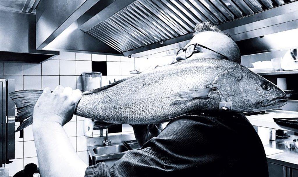 un homme tenant un gros poisson sur son épaule dans une cuisine de restaurant