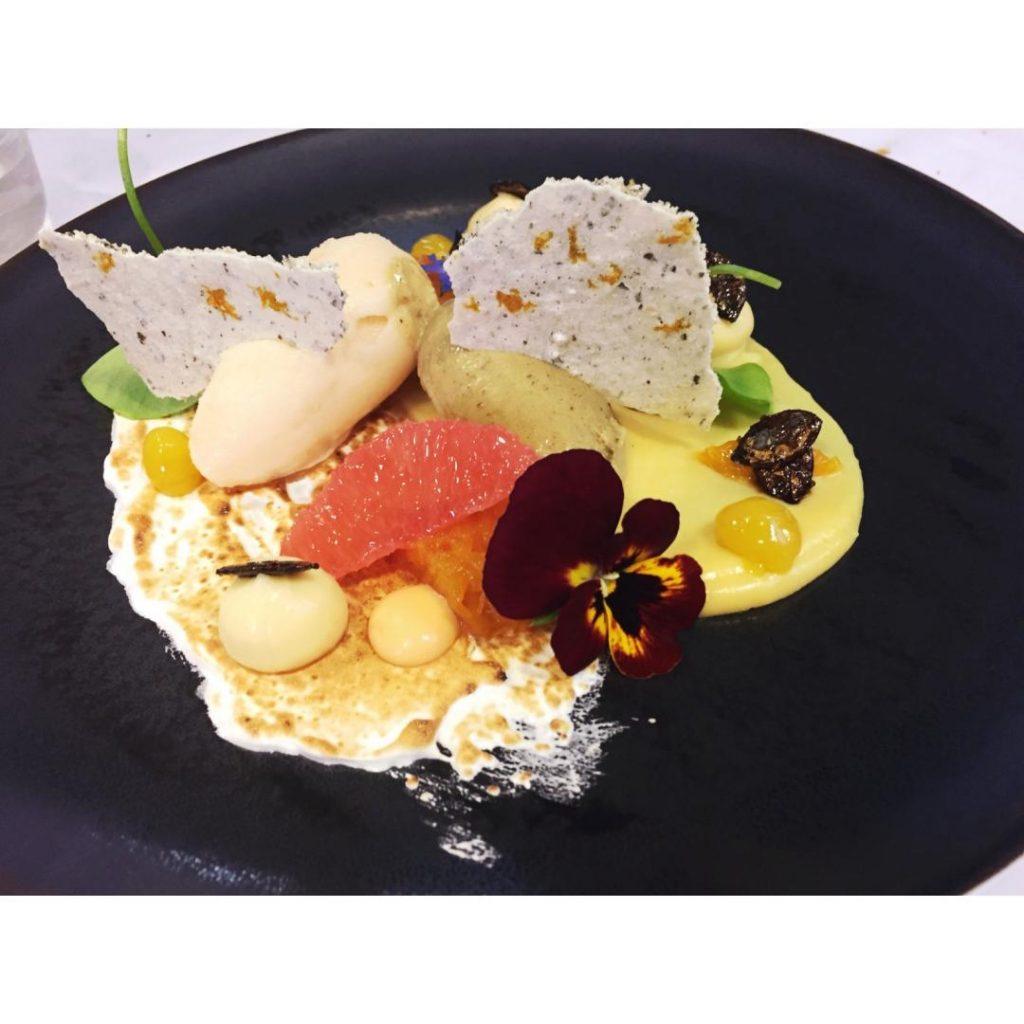 assiette noire avec une présentation de glace et fruits et une crème anglaise restaurant l'impertinent