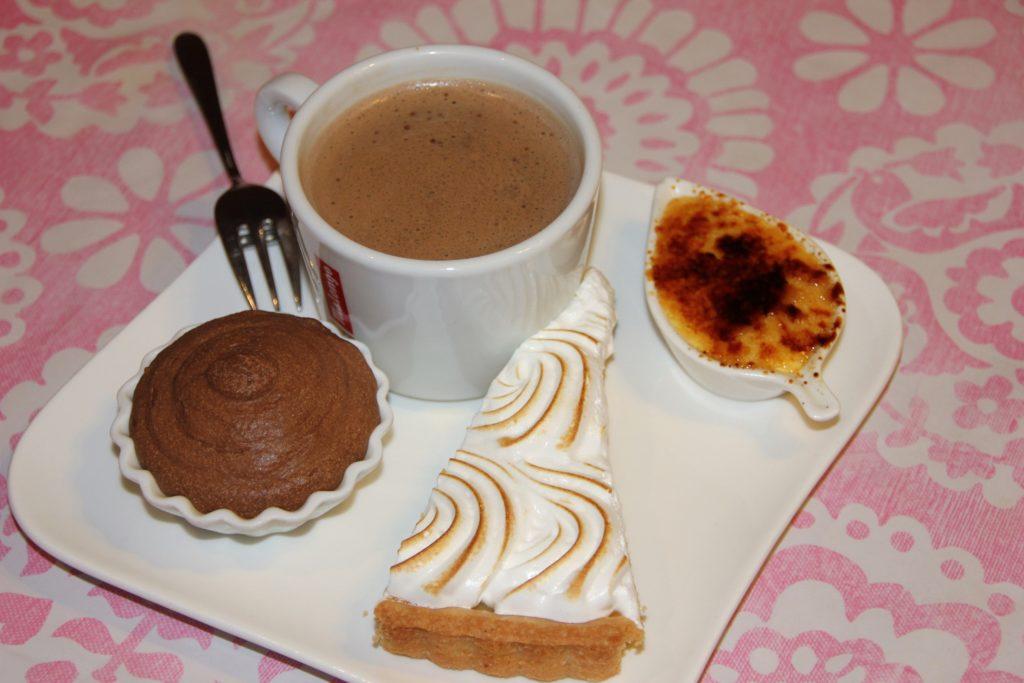 café gourmand au déjeuner sur l'herbe, assiette blanche avec une tasse à café et des petits gâteaux cambo les bains