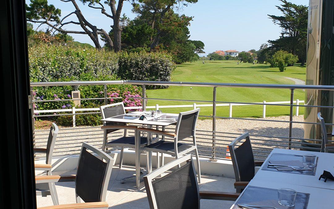 une terrasse qui donne sur le golf de biarritz, avec de chaises et des tables en métal