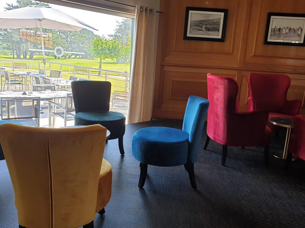 3 fauteuils de couleurs dans un petit salon avec vue sur le golf de biarritz