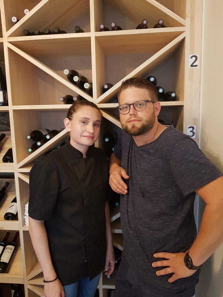 un homme et une femme habillé de noir devant la cave à vin
