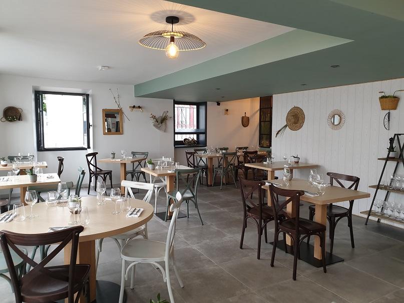 salle de restaurant avec des tables en bois clair murs blancs et décoration vertes