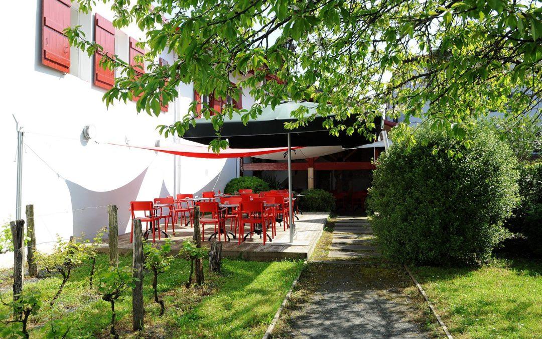 des tables rouges dans un jardin avec la vue sur la montagne restaurant Chilhar à Espelette